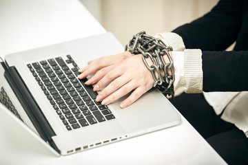 photo of female hand chained up to laptop