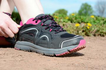 Sportlerin schnürt Laufschuhe zum Joggen