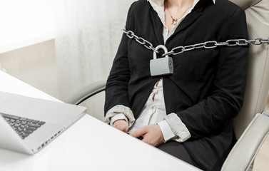 photo of businesswoman tied to chair by metal chain