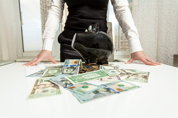 lady behind table with piggy bank and money