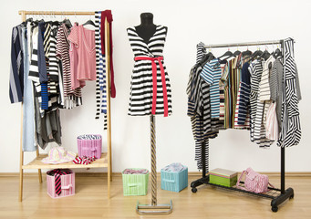 Closet with striped clothes arranged on hangers and a mannequin