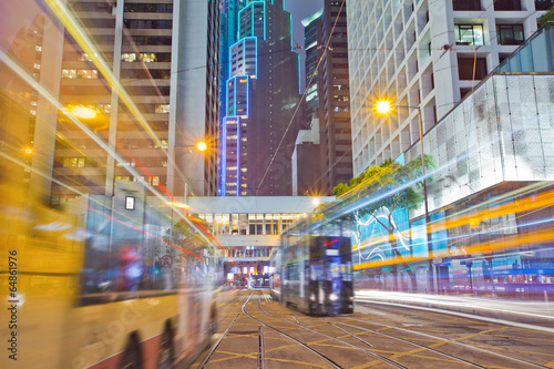 Juliste tram and bus on the road the night of Hong Kong