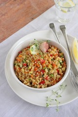 Portion of homemade quinoa salad with vegetables and lemon