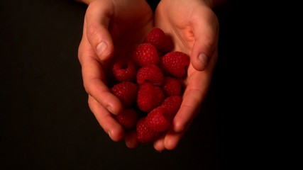 Woman spilling raspberries from her hands