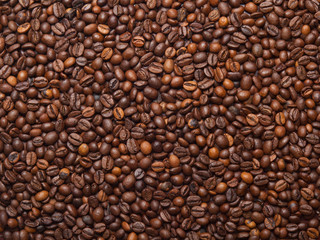Numerous coffee beans which have been scattered all over the sur