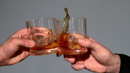 Men clinking whiskey glasses on grey background