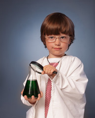 boy studying a substance in a test tube with a magnifying glass