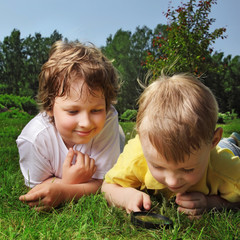 two boys with magnifying glass outdoors