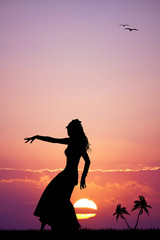 Hawaiian woman dancing at sunset