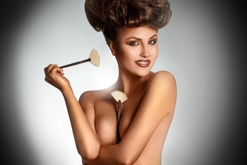 Portrait of sexy brunette with brushes smiling on camera