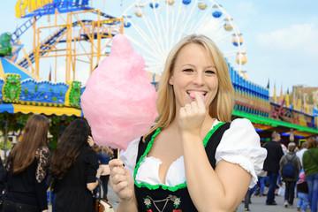 Frau im Dirndl auf Oktoberfest isst Zuckerwatte