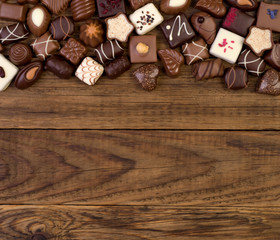 Various chocolates on wooden background