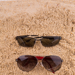 Pair of sunglasses on beach sand