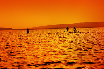 three stand-up-paddler on the lake at sunset