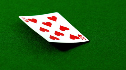 Eight of hearts falling on casino table