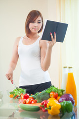Young woman reads cookbook