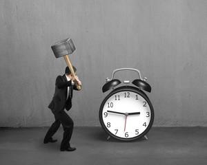 Hitting alarm clock with sledge hammer