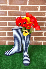 Composition of colorful tulips in rain boots