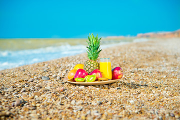 Plate of fresh fruit on the beach