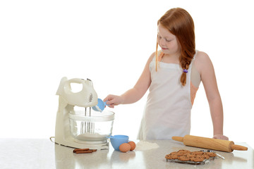 girl adding flour to stand mixer