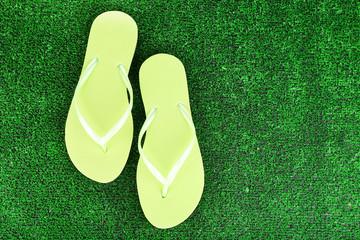 Bright flip-flops on green grass background