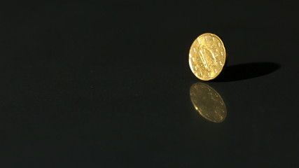 Euro coin spinning on black surface