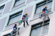 Worker are painting the color in high rise buildings. - 64873550