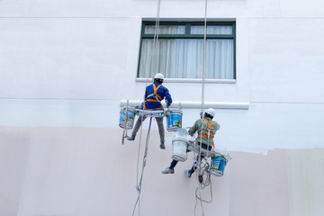 Two worker are painting the color in high buildings - Rise occup