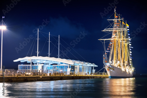 Ancient sailing ship in a modern port