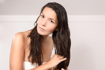 Junge Frau in Unterwäsche pflegt ihre Haare