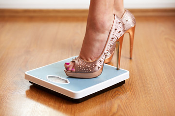 Female feet in golden stilettos on a weight scale