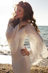 beautiful woman in white dress posing on beach