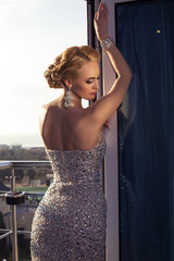 beautiful woman with blond hair in elegant dress and diamonds