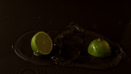 Lime halves dropping on wet black surface