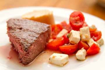t-bone steak with tomatoes and feta cheese