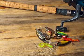 spoon, wobblers, silicone bait and spinning on a wooden table