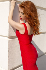 sexy woman with red hair and freckles in elegant dress