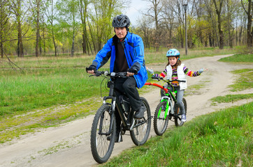 Happy father and child on bikes, family cycling ourdoors
