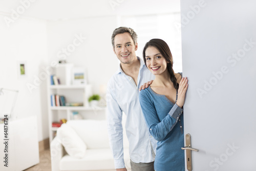 Cheerful couple inviting people to enter in home - 64876734