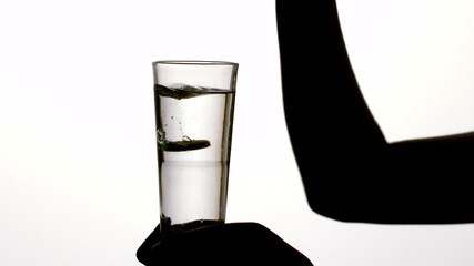 Silhouette of woman dropping vitamin tablet in water