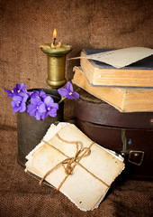 Старые фотографии, книги и медный подсвечник