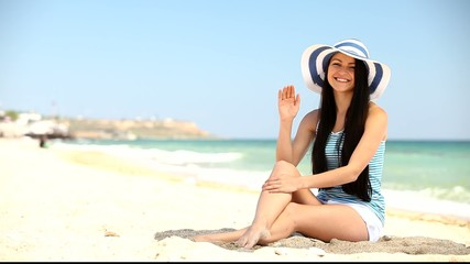 Young brunette girl on the beach in summer time.