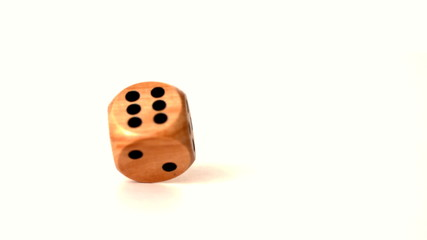 Wooden dice spinning on white surface