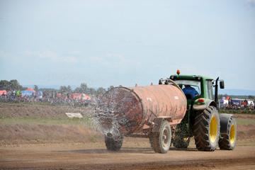 tractor con remolque regando circuito de tierra antes de carrera