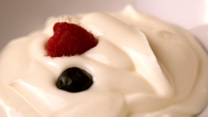 Berries falling onto whipped cream