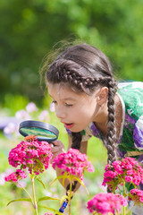 girl looking through magnifying glass on flower