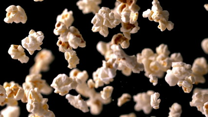 Popcorn bouncing against black background