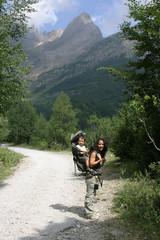 Madre llevando hijo en mochila por camino de montaña