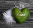 Grünes Herz mit dem Wort Glück auf Holz