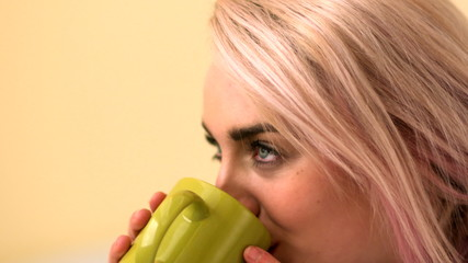 Pretty young blonde sipping from mug